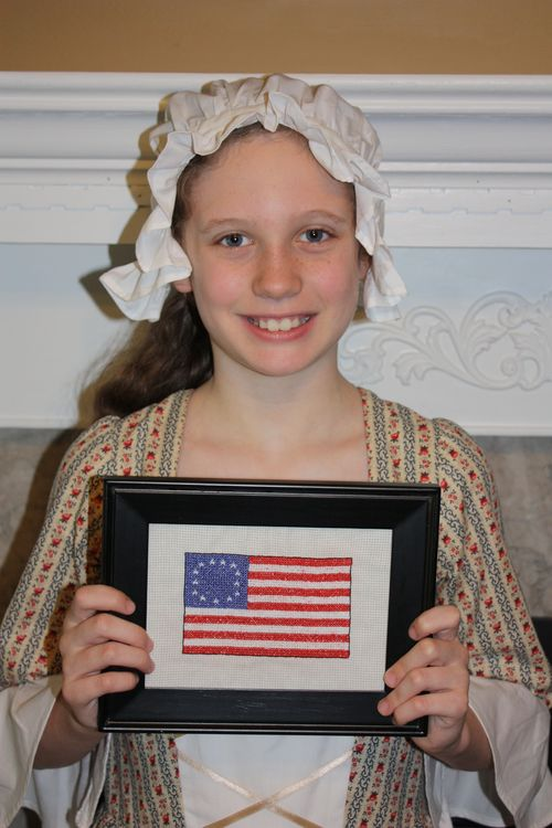 Olivia with her cross stitching of the Betsy Ross flag